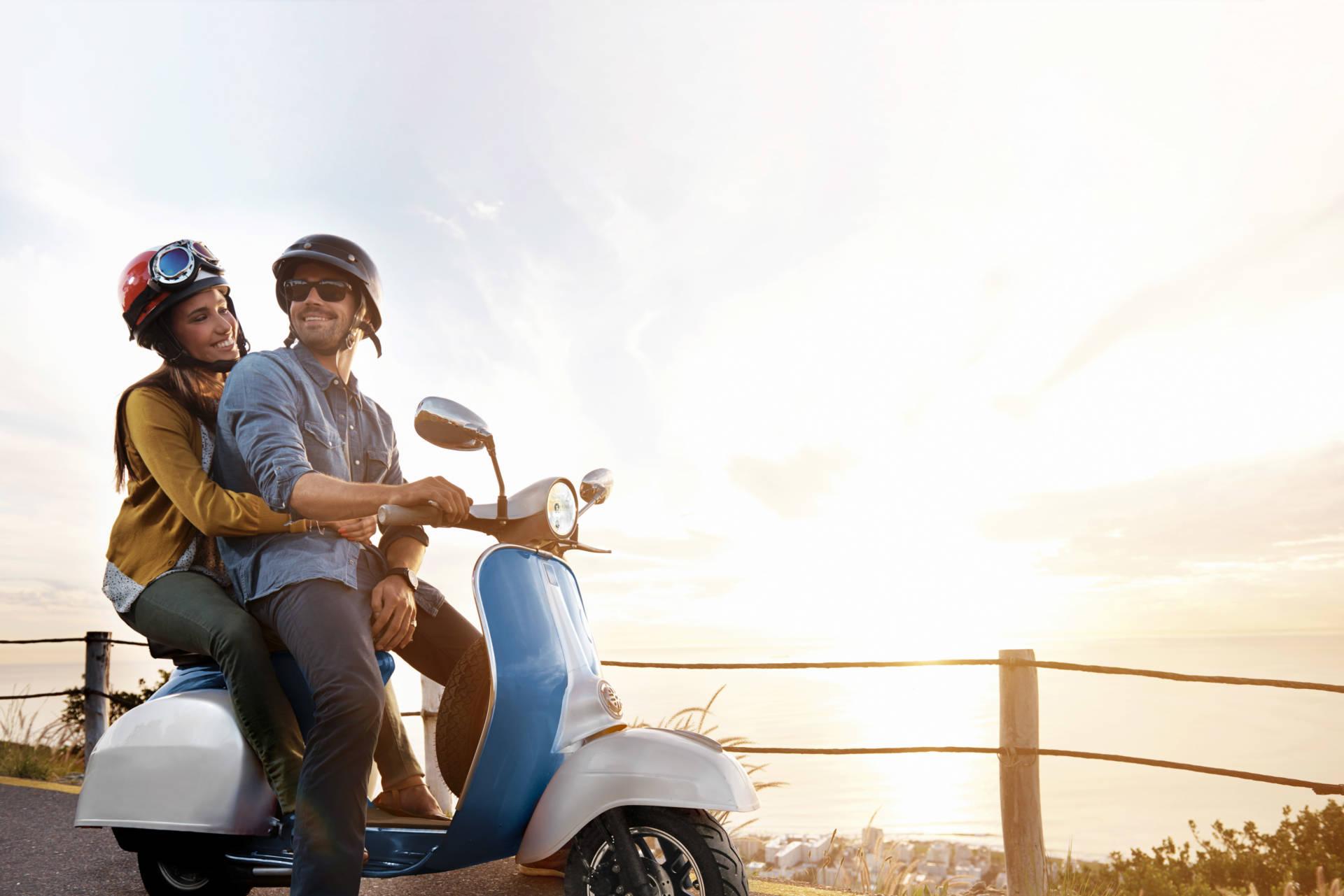 E-Roller laden: Mann und Frau auf E-Roller