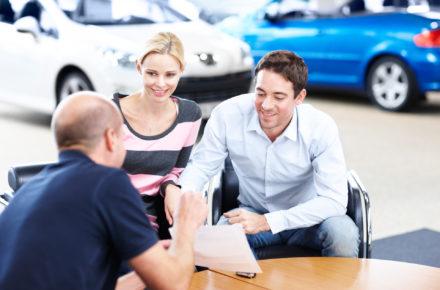 Elektroauto gebraucht kaufen: Junges Paar lässt sich vom Verkäufer beraten