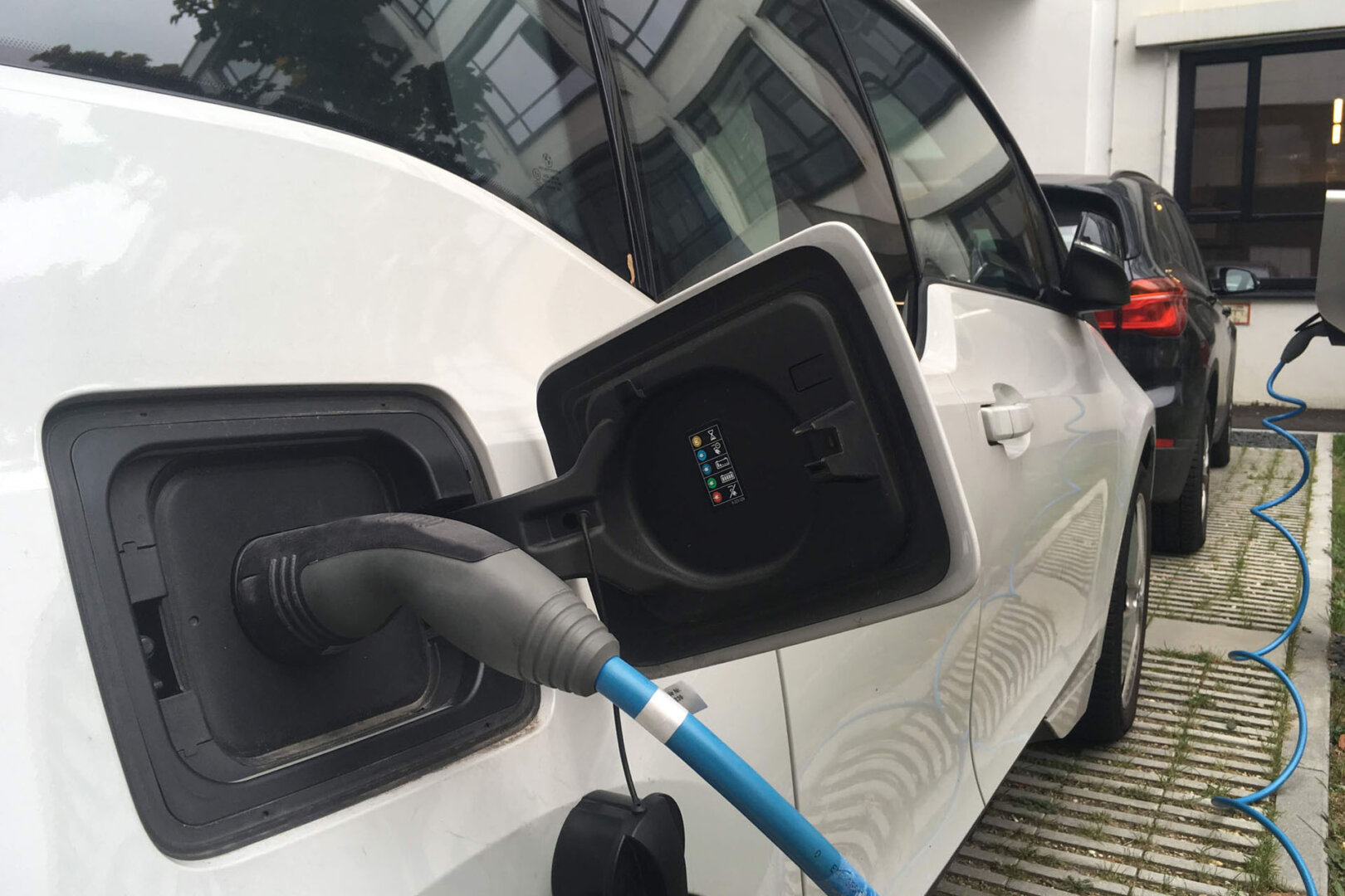 Elektroauto an Ladesäule angeschlossen, davor im Vordergrund ein Benzinauto