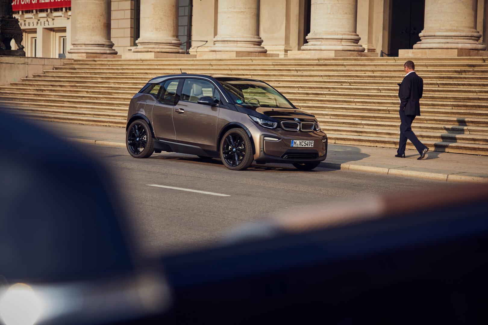 BMW Elektroauto steht am Straßenrand daneben geht ein Mann.