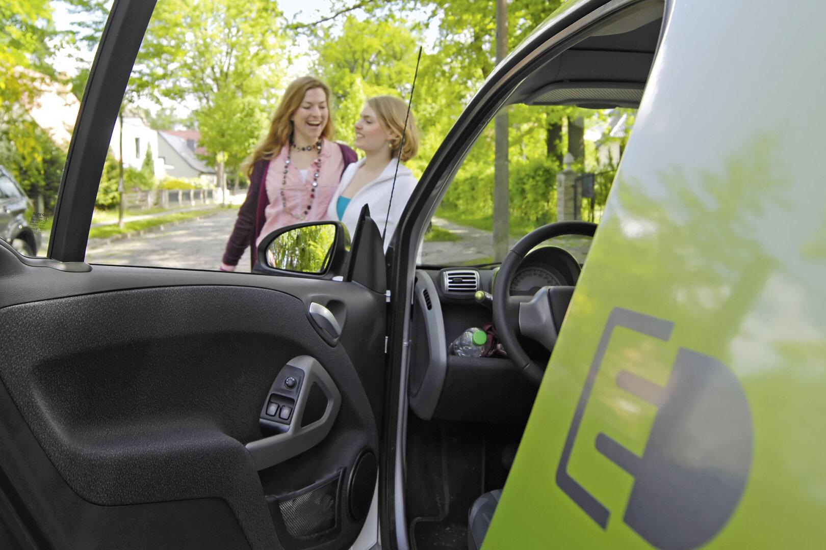 Frauen stehen vor einem Elektroauto
