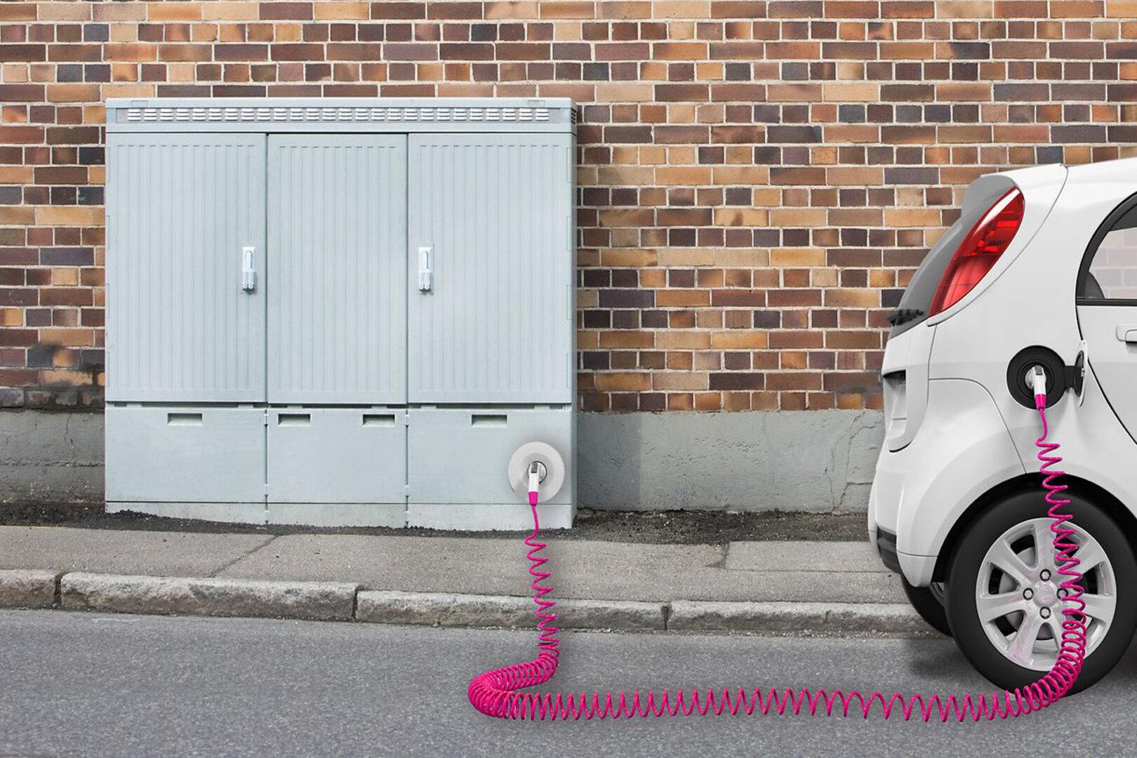 Elektroauto zum Laden an grauen Verteilerkasten angeschlossen.