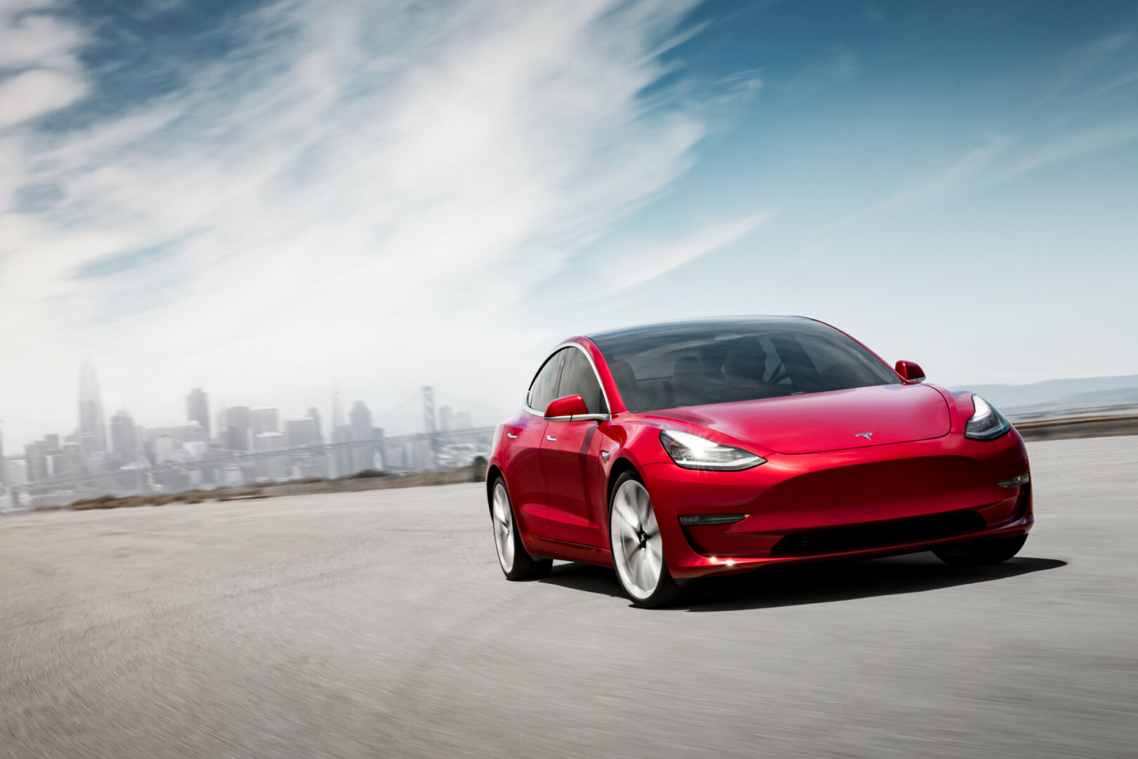 Roter Tesla Model 3 fährt auf der Straße