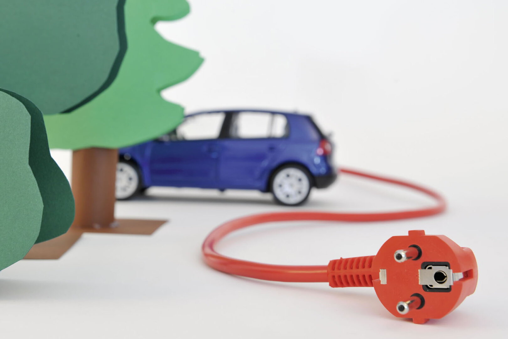 Auto mit regulärem Stecker, davor Bäume