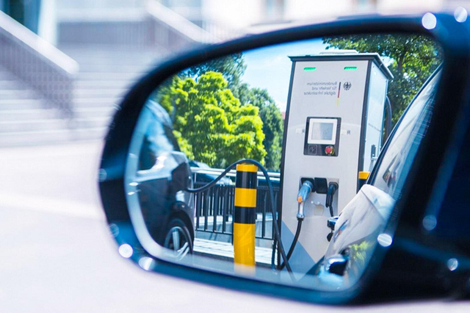 Durch Autoseitenspiegel sieht man eine Ladesäule für E-Autos.