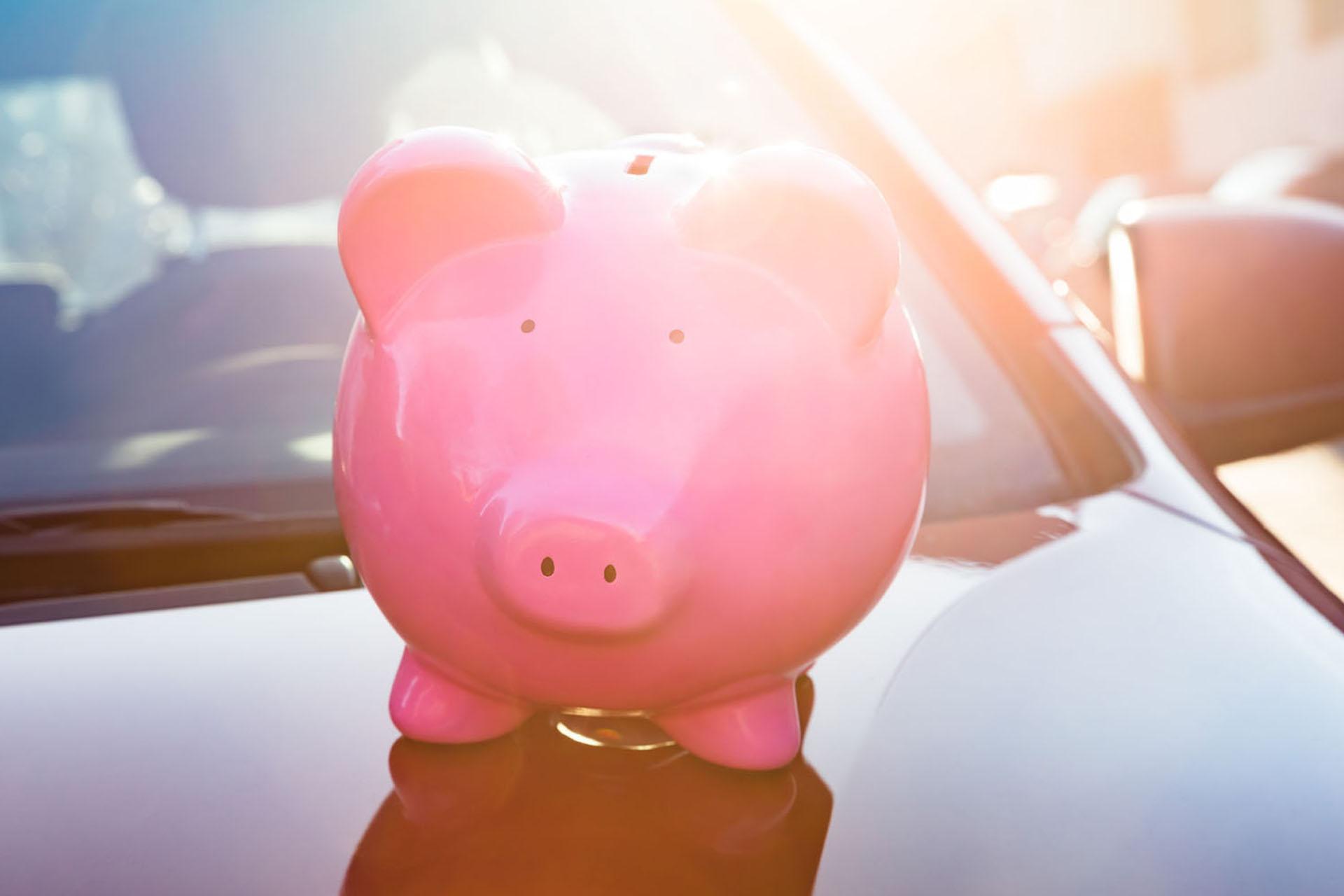 Preise für E-Autos: Rosa Sparschwein auf einer Motorhaube.