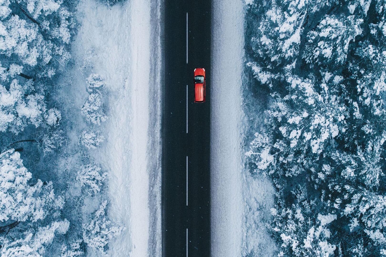 Elektroauto im Winter: Fahrzeug auf Straße in verschneiter Winterlandschaft