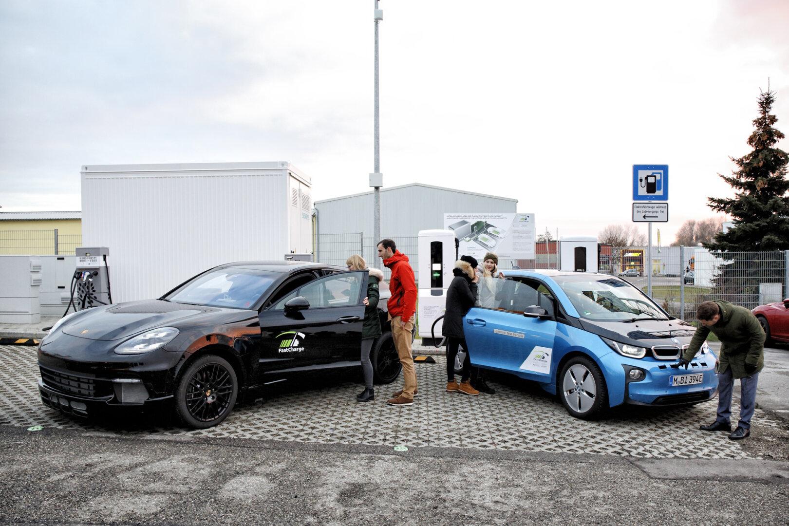 Zwei E-Autos stehen vor einer Ladestation.