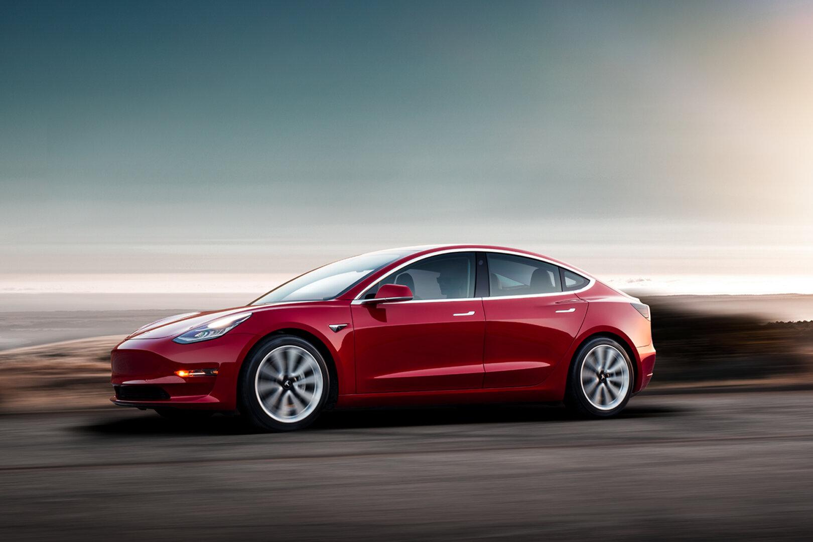 Tesla Model 3 in rot fährt eine Straße entlang