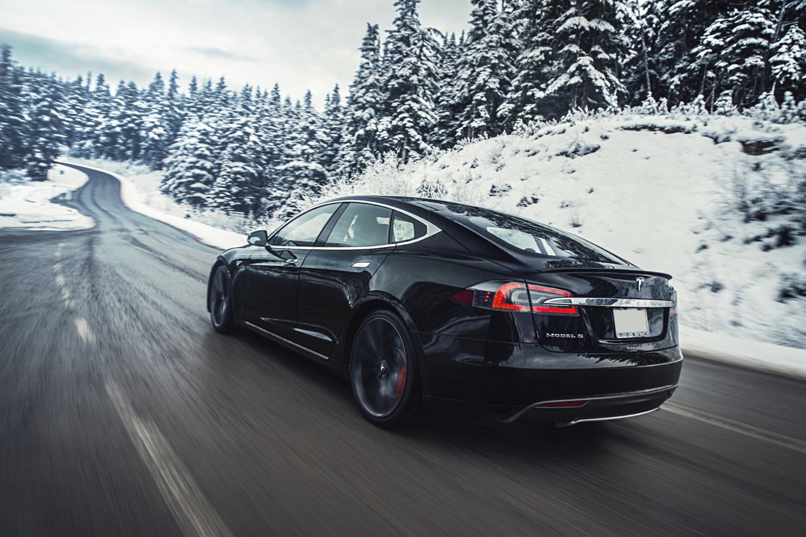 Schwarzer Tesla im Winter auf einer Straße.