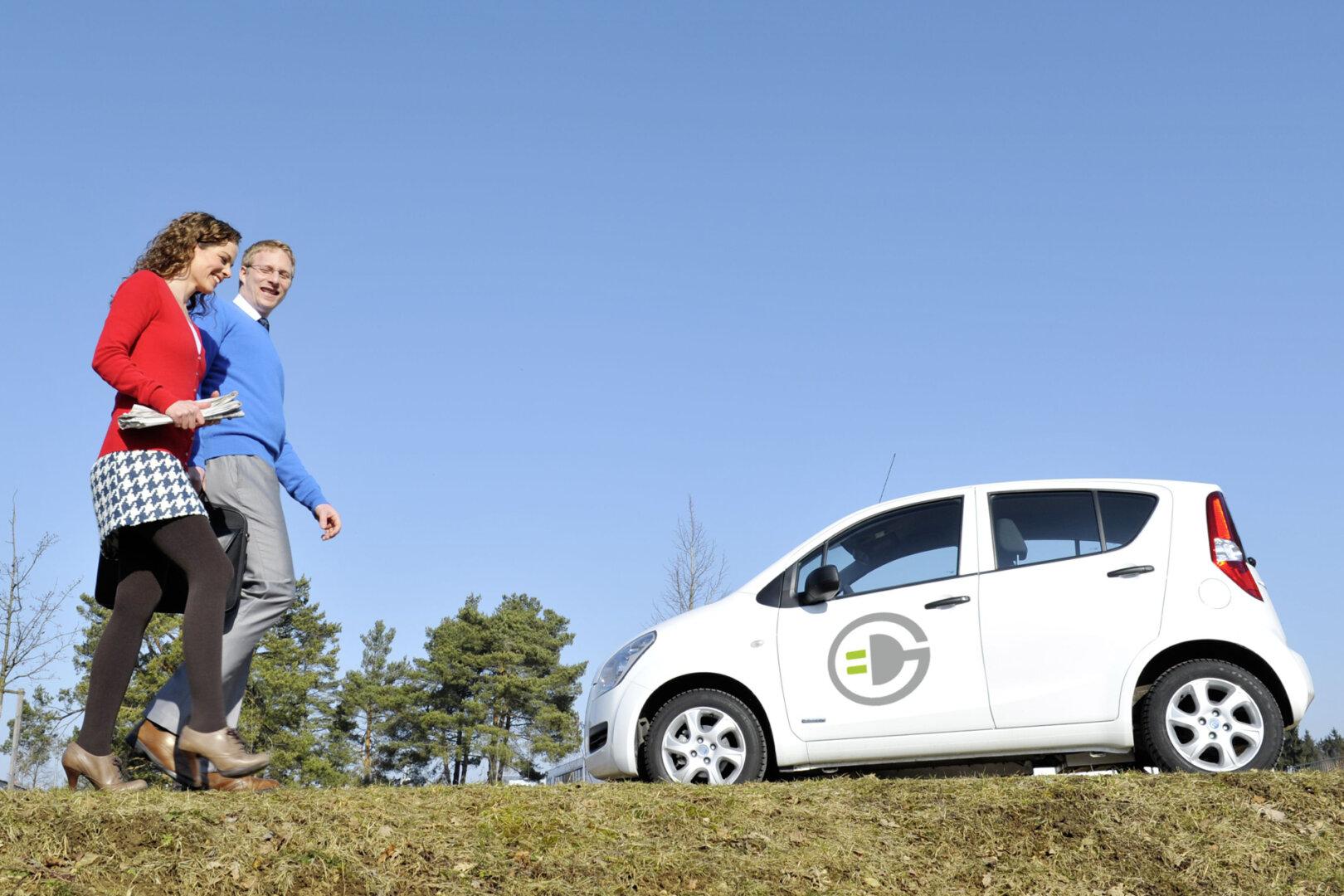 Elektroauto steht, davor bewegen sich zwei Personen lächelnd