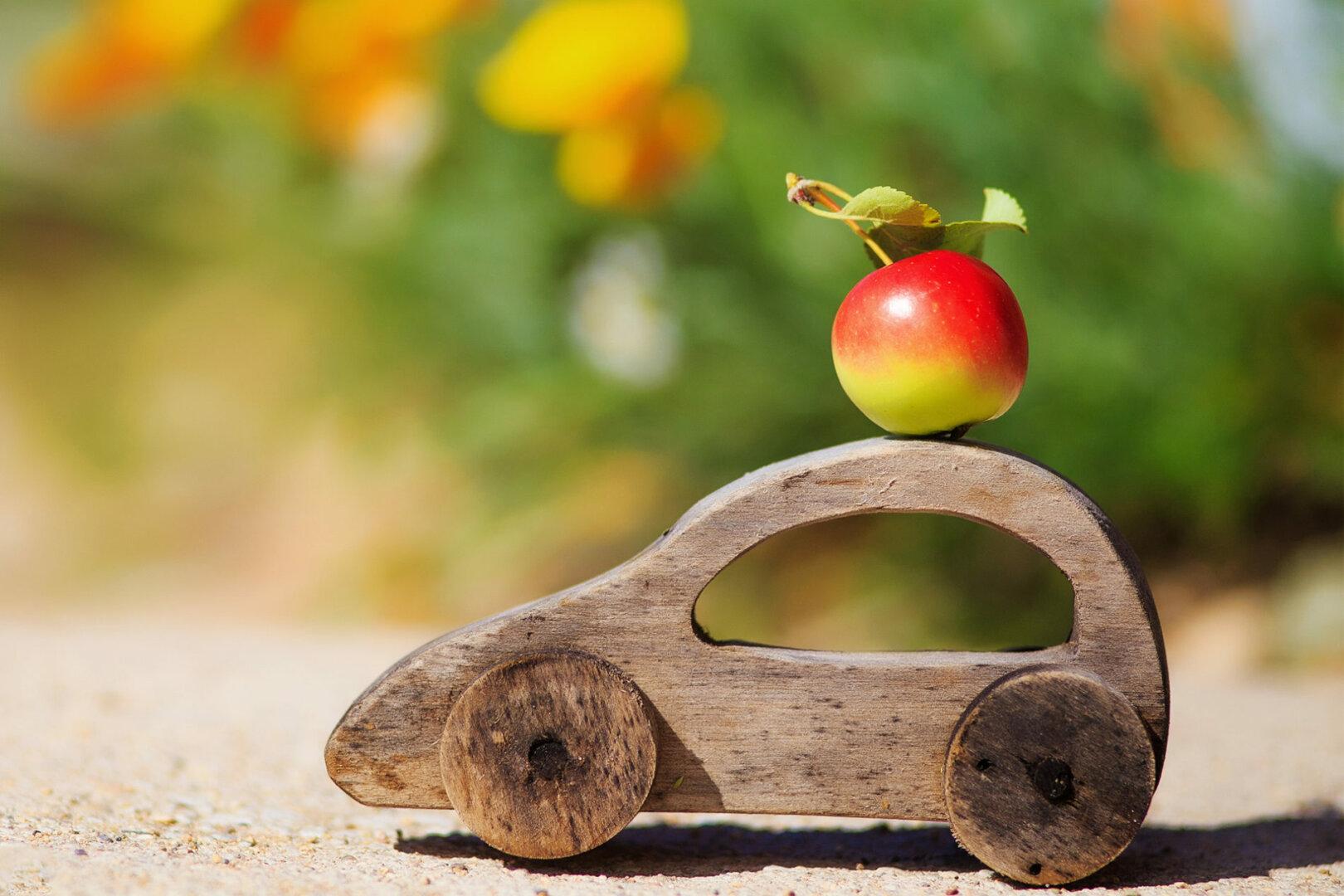 Holzauto mit Apfel auf dem Dach