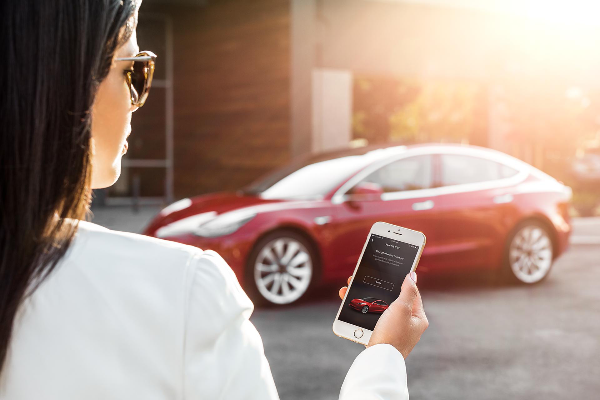 Frau schaut auf App im Handy, die Tesla Model 3 steuert