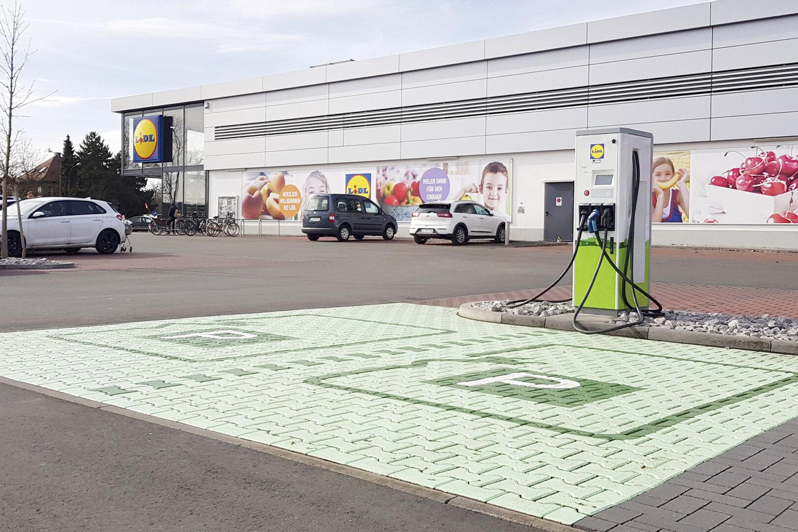 Grüne Ladesäule auf einem Lidl Parkplatz.