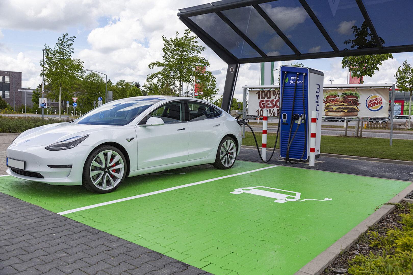 Weißer Tesla lädt an Burger-King Ladestation