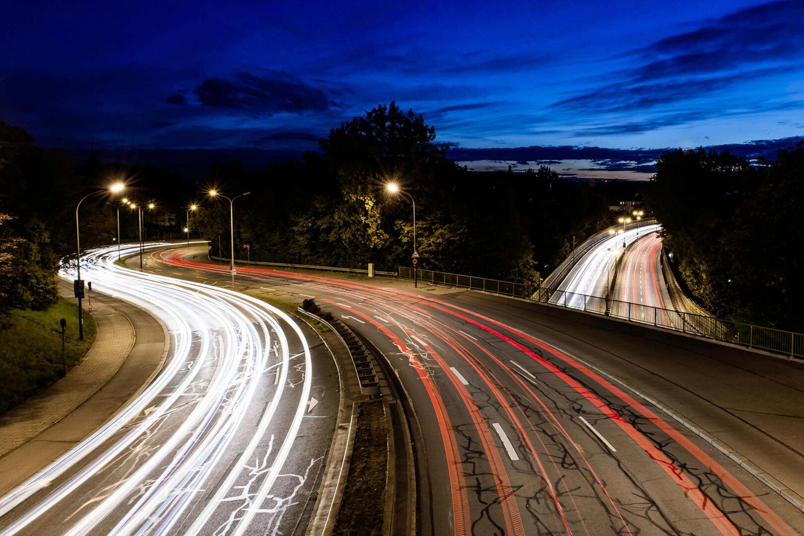 Eine Straße in der Nacht auf der Lichtlinien zu sehen sind.