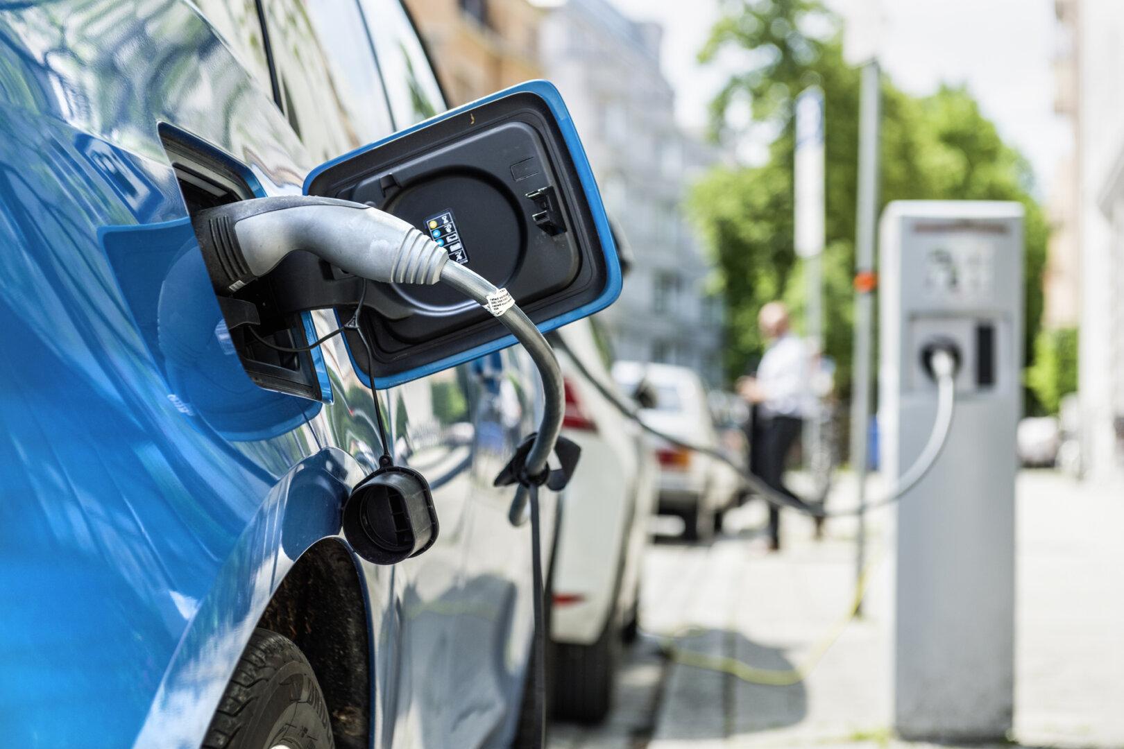 Blaues Elektroauto wird an öffentlicher Ladestation aufgeladen