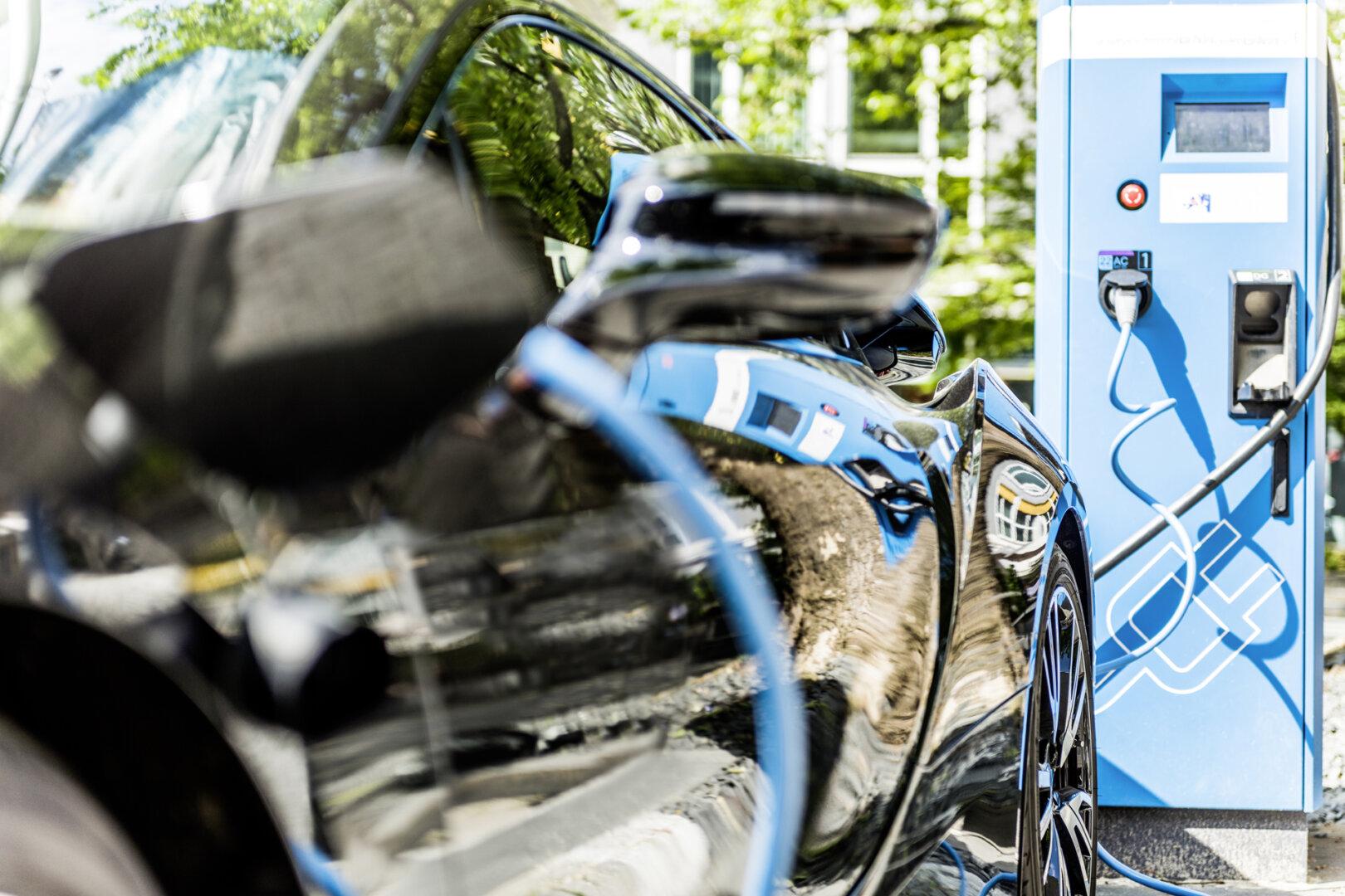 Schwarzes Elektroauto lädt an öffentlicher Ladestation