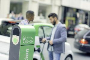 Zwei Männer laden Ihr Elektroauto an einer E-Ladestation