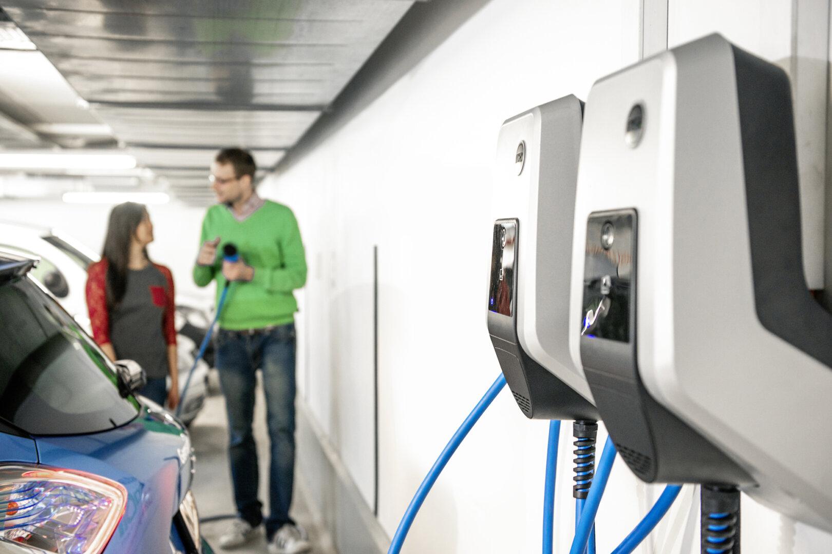Frau und Mann laden mit MENNEKES Wallbox blaues Renault Elektroauto