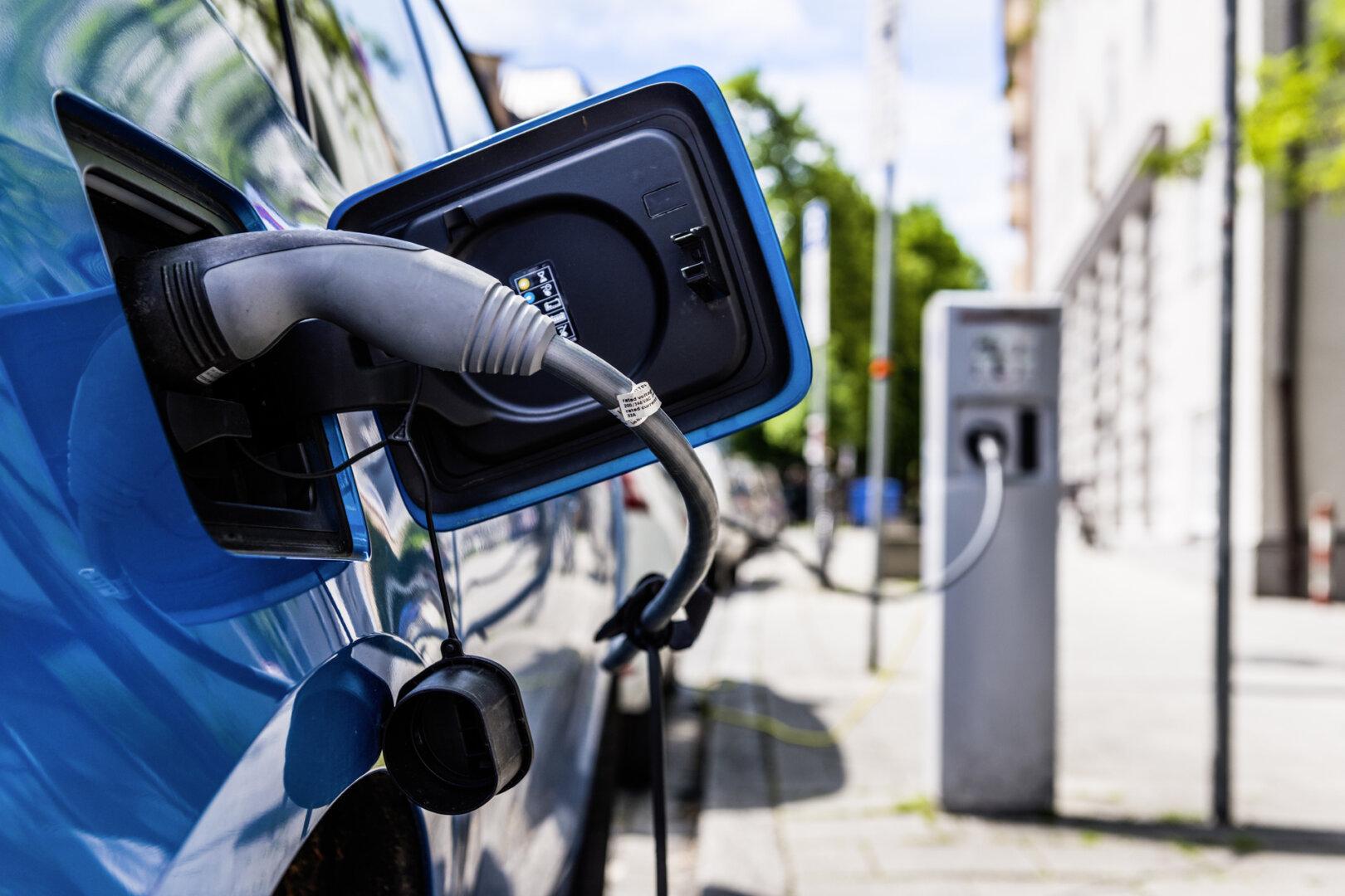 Blaues Elektroauto lädt an einer öffentlichen Ladestationen
