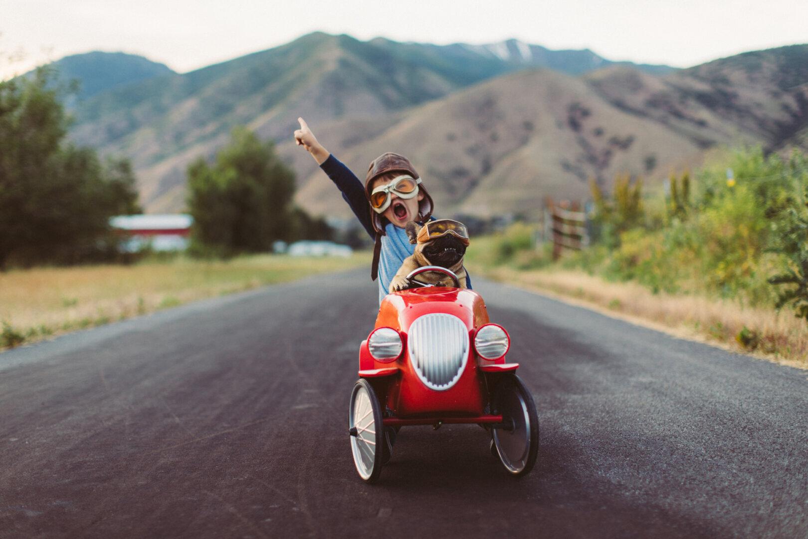 Kleiner Junge mit Fliegerbrille fährt ein rotes Spielzeugauto