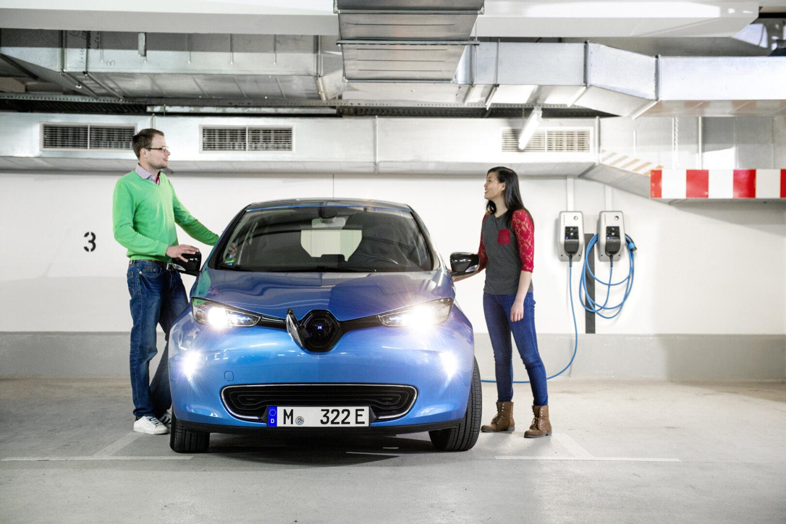 Frau und Mann stehen an blauem Renault Elektroauto während es an Wallbox lädt