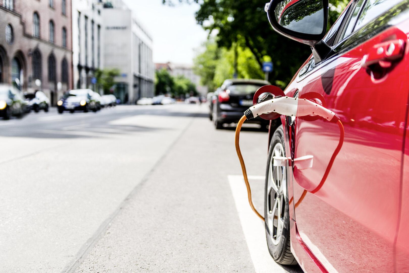 Rotes Elektroauto lädt auf öffentlichem Parkplatz in der Stadt