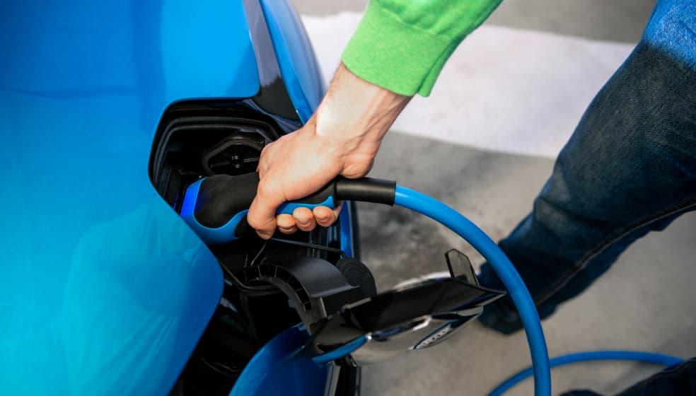 Blaues Renault Elektroauto wird von Mann geladen