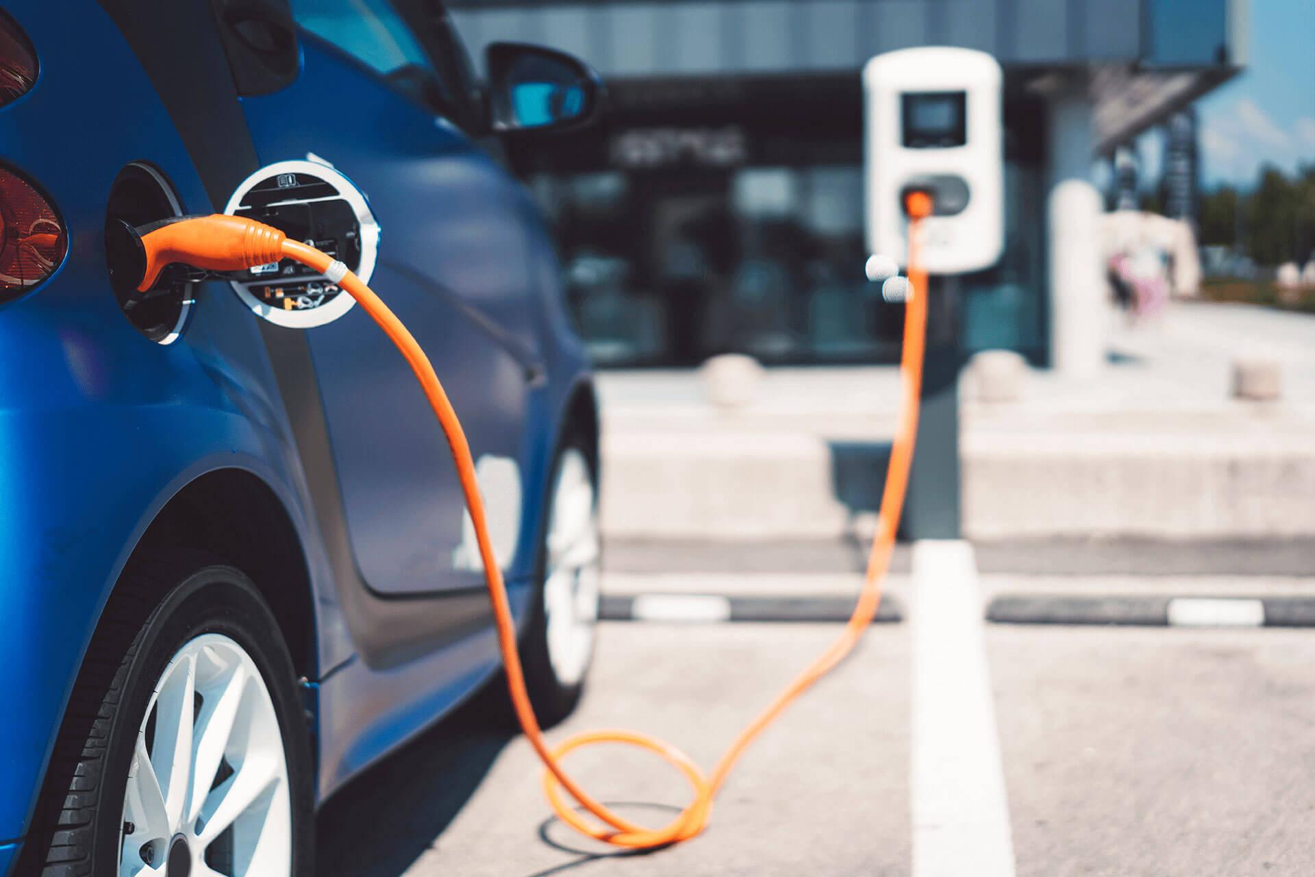 Blaues Elektroauto lädt auf einem öffentlichen Parkplatz mit orangenen Kabel